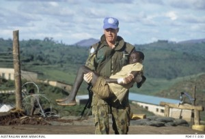 Trooper (Tpr) Jon Church carries an injured Rwandan child.